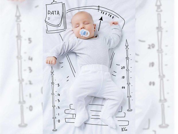 neonato con ciuccio in bocca è disteso su una coperta ornata da disegni che riproducono una bilancia