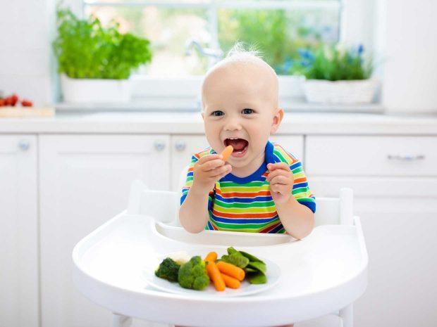 bambino seduto sul seggiolone mangia delle carote e dei broccoletti