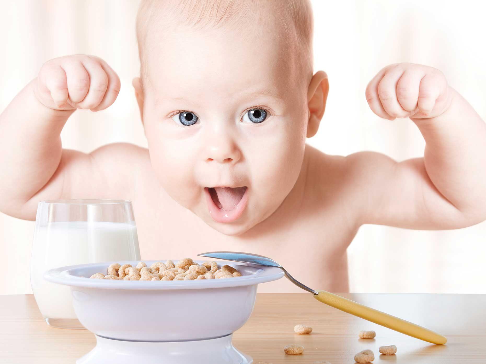 bambino esulta davanti una ciotola di cereali e un bicchiere di latte