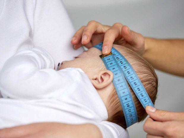adulto misura il cranio del neonato con un metro azzurro