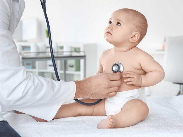 bambino guarda pediatra che ausculta i suoi battiti con lo stetoscopio
