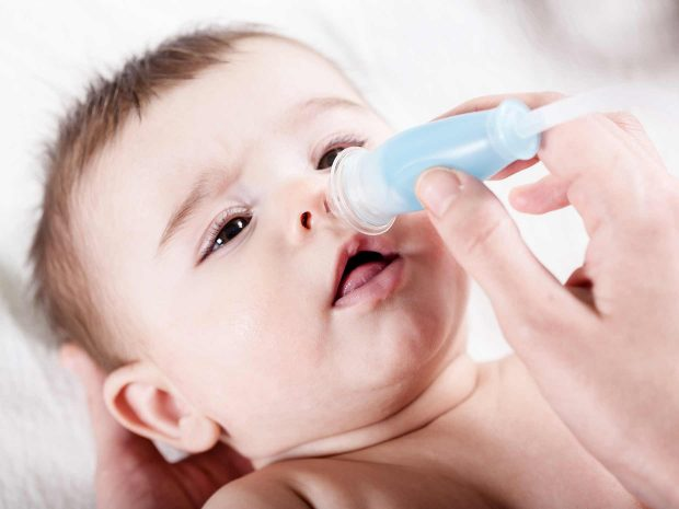 pulizia del naso di un bambino piccolo tramite aspiratore nasale a bocca