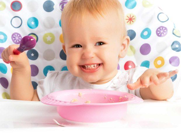 bambino piccolo sorride felice mangiando la pastina sul seggiolone