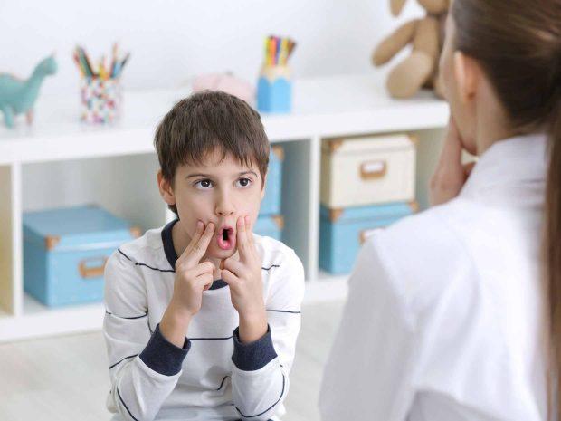 bambino svolge esercizi di logopedia schiacciando le guance con le dita
