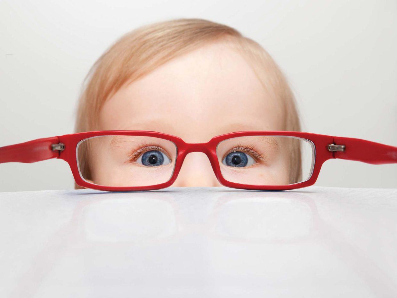 viso di bambino in primo piano con occhiali da vista rossi