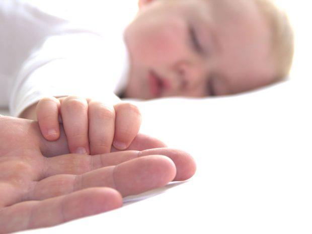 neonato dorme stringendo con la mano le dita del papà