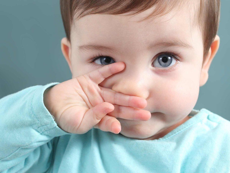 bambino con maglietta azzurra si gratta il naso con la mano