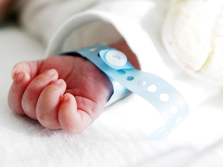 mano di neonato appena nato in ospedale con al polso il braccialetto di riconoscimento