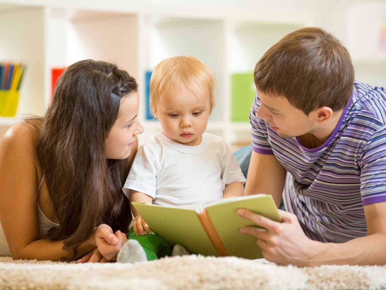 mamma e papà distesi sul tappeto leggono libro al figlio piccolo